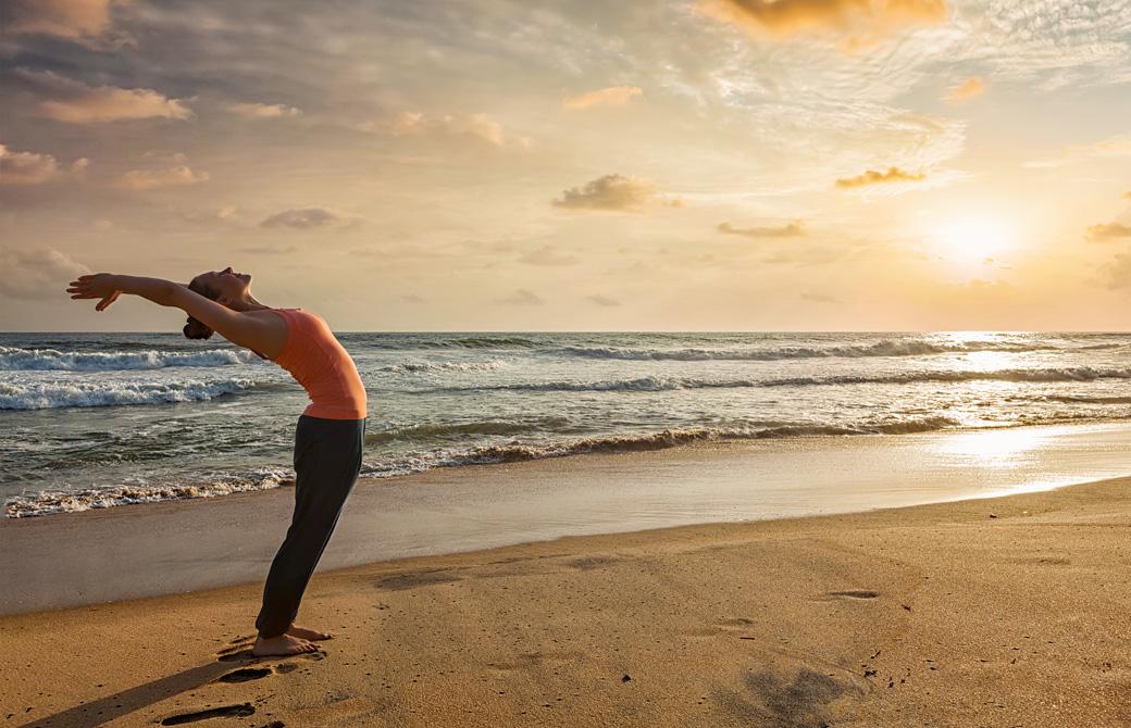 浜辺で朝日に向かって太陽礼拝をしている女性