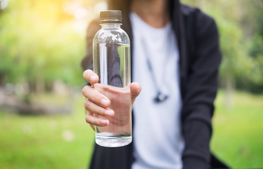 水のボトルを差し出している女性の上半身