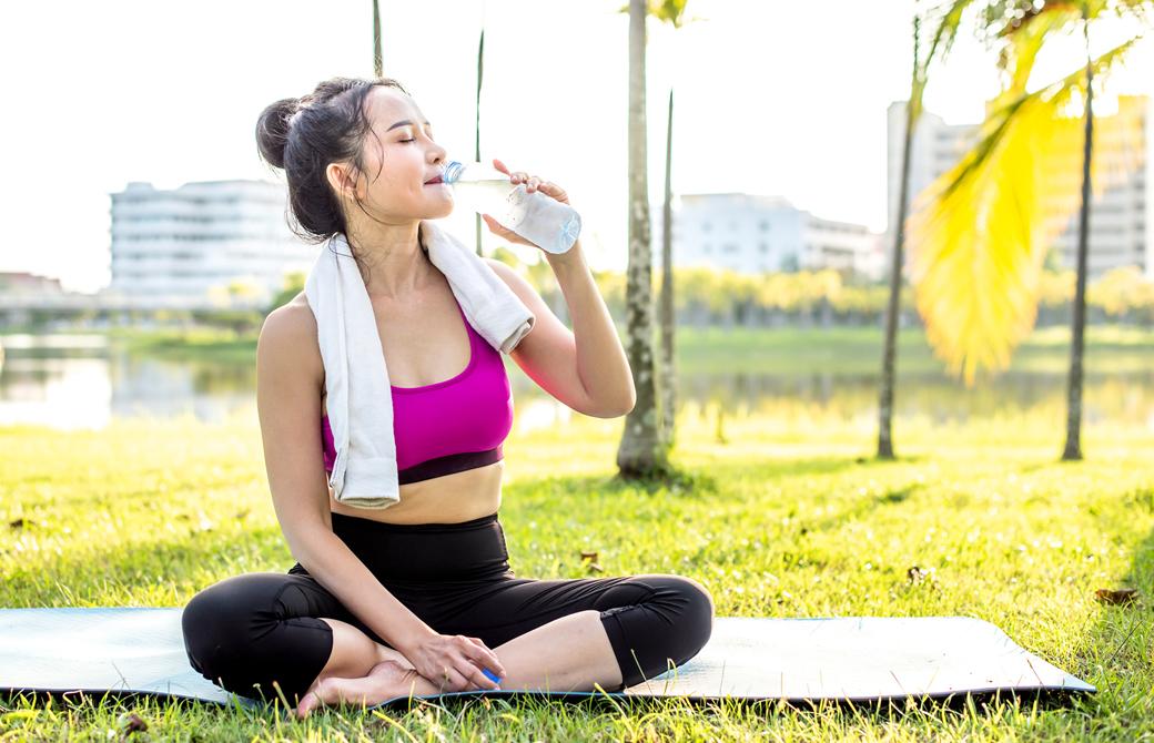 屋外の芝生に座って水をボトルから飲んでいるヨガウェアの女性