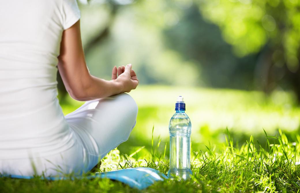 木漏れ日のある公園の芝生であぐらをして水のボトルを横に置いている女性