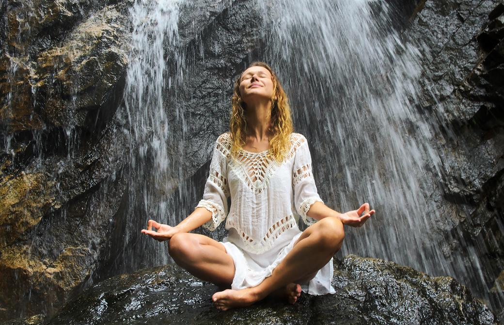 女性が滝に打たれて瞑想をしている