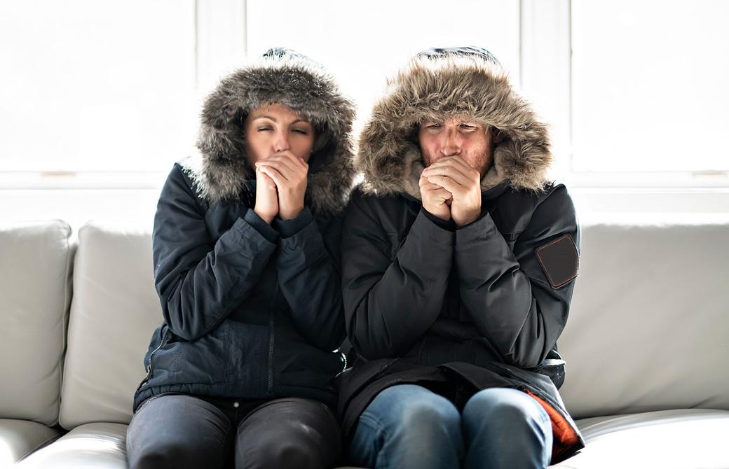 ソファでダウンジャケットを着た男女が寒そうに手をこすり合わせている