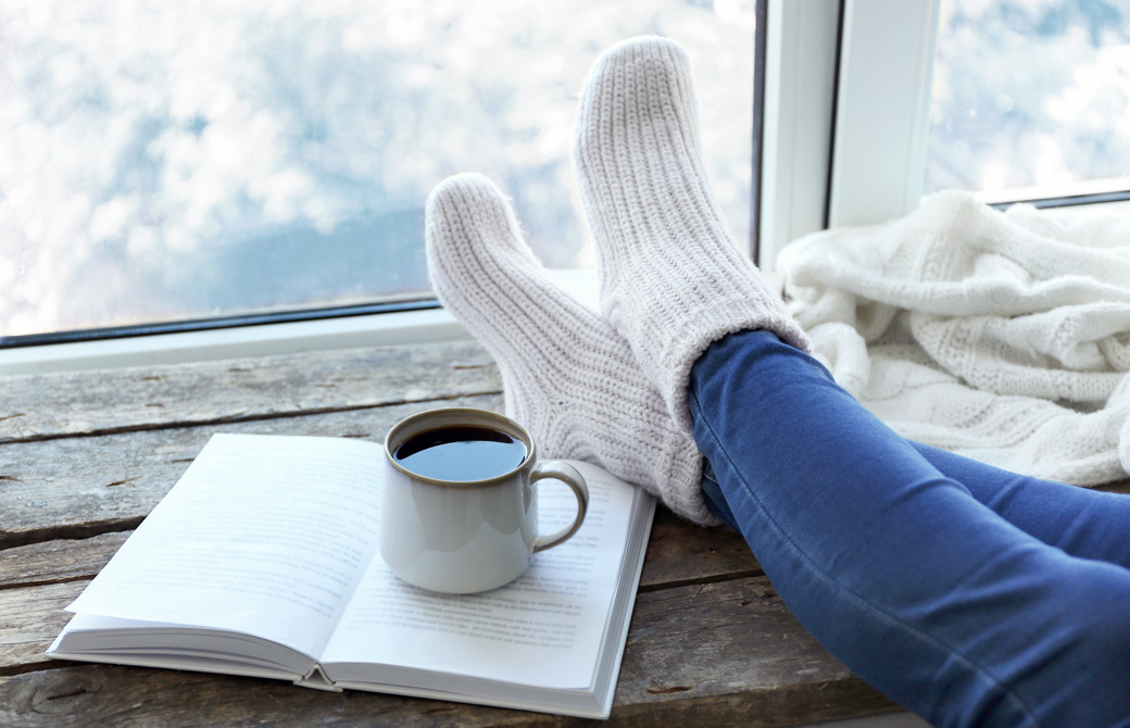 窓際で本を広げてマグカップを置きくつろいでいる女性の足下
