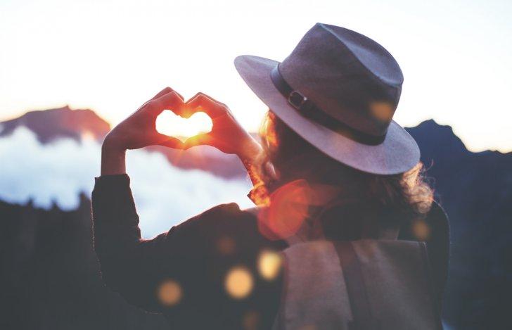 帽子をかぶった女性が夕陽越しに手でハートのかたちをつくっている