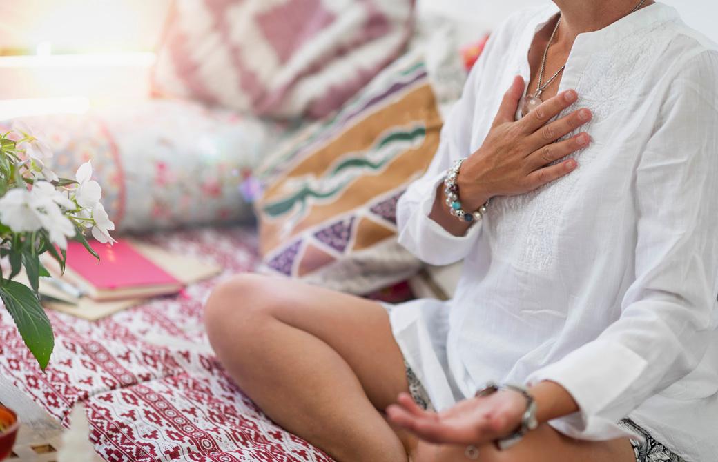カラフルなクッションに囲まれて瞑想をする女性