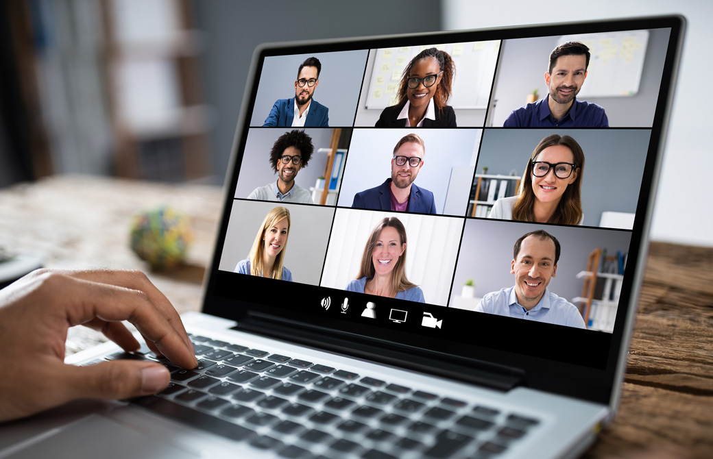 パソコンの画面に映し出されたオンライン会議の模様とパソコンの持ち主の左手