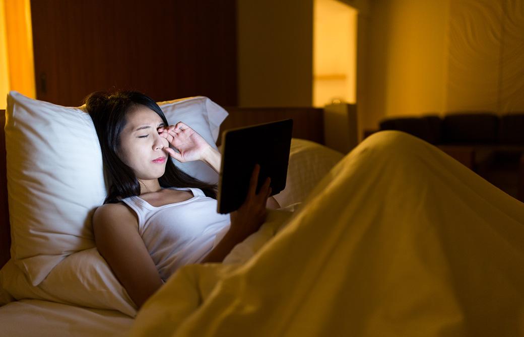 ベッドの上で夜更かししてタブレットを見ながら目をこすっている女性
