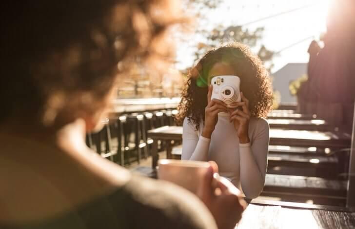 インスタントカメラで友達を撮影している女性