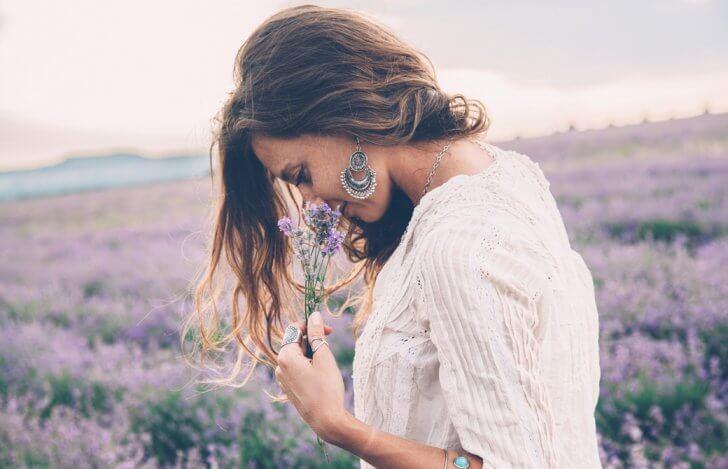 ラベンダー畑で香りを楽しんでいる女性の横からの姿