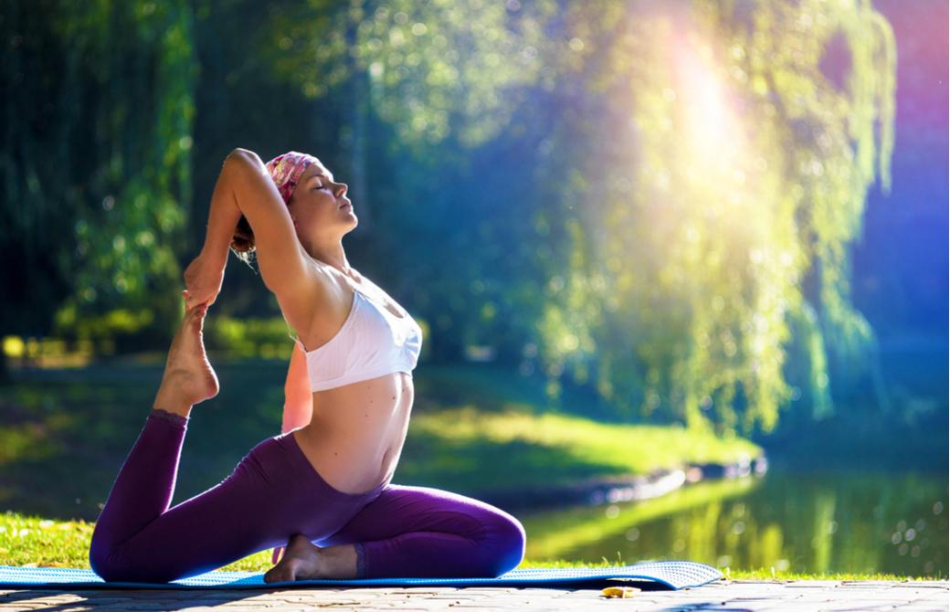 朝日を浴びながら公園でヨガをする女性