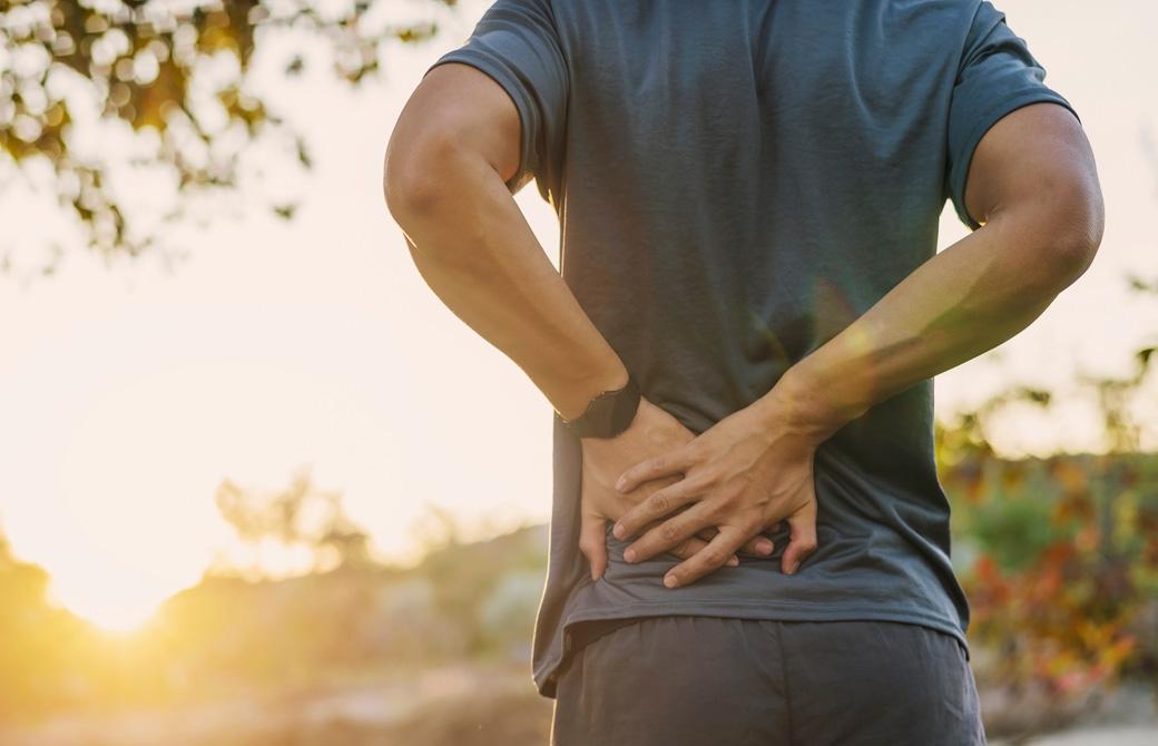 腰痛で腰をおさえている男性の後ろ姿