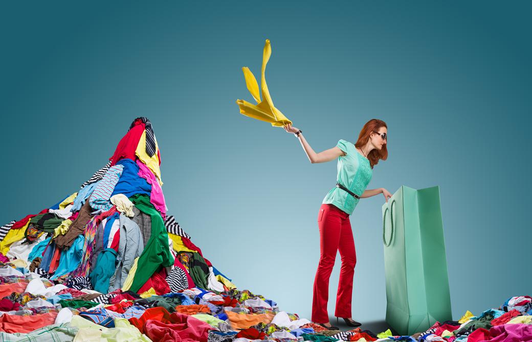 大きな紙袋から洋服を引っ張り出して放り投げて積んでいる女性