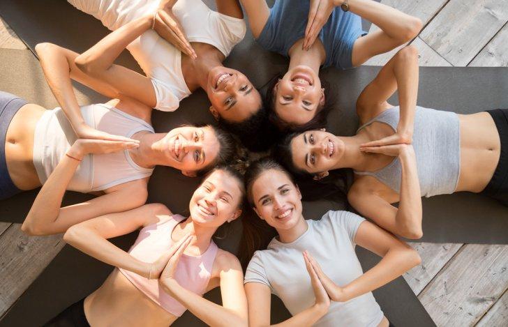 マットの上に輪になって横になり胸で合掌して笑顔の5人の女性たち