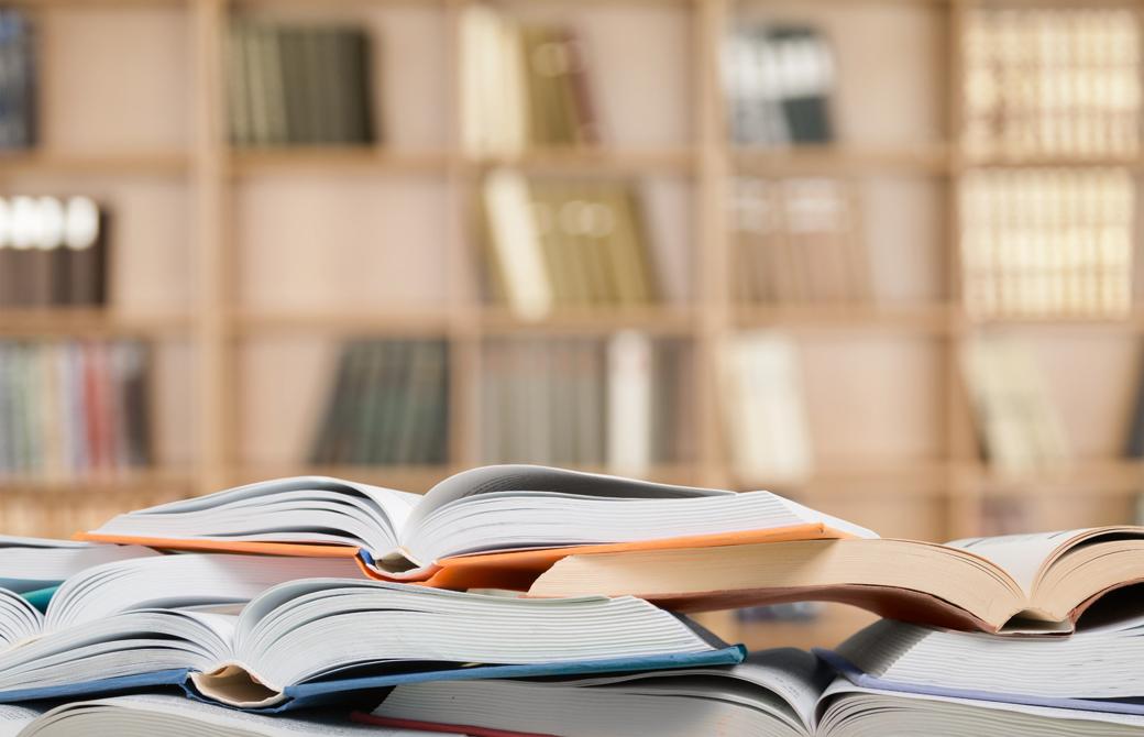 図書室で本が開かれ積まれている