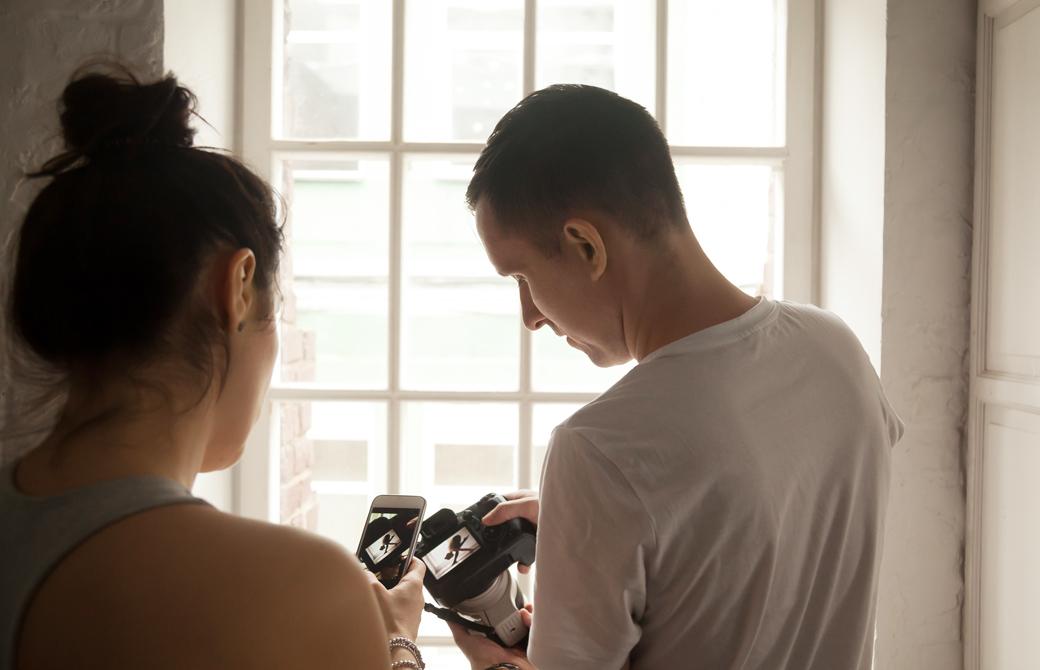 窓際でカメラのファインダーを見ながら写真を見比べている男女