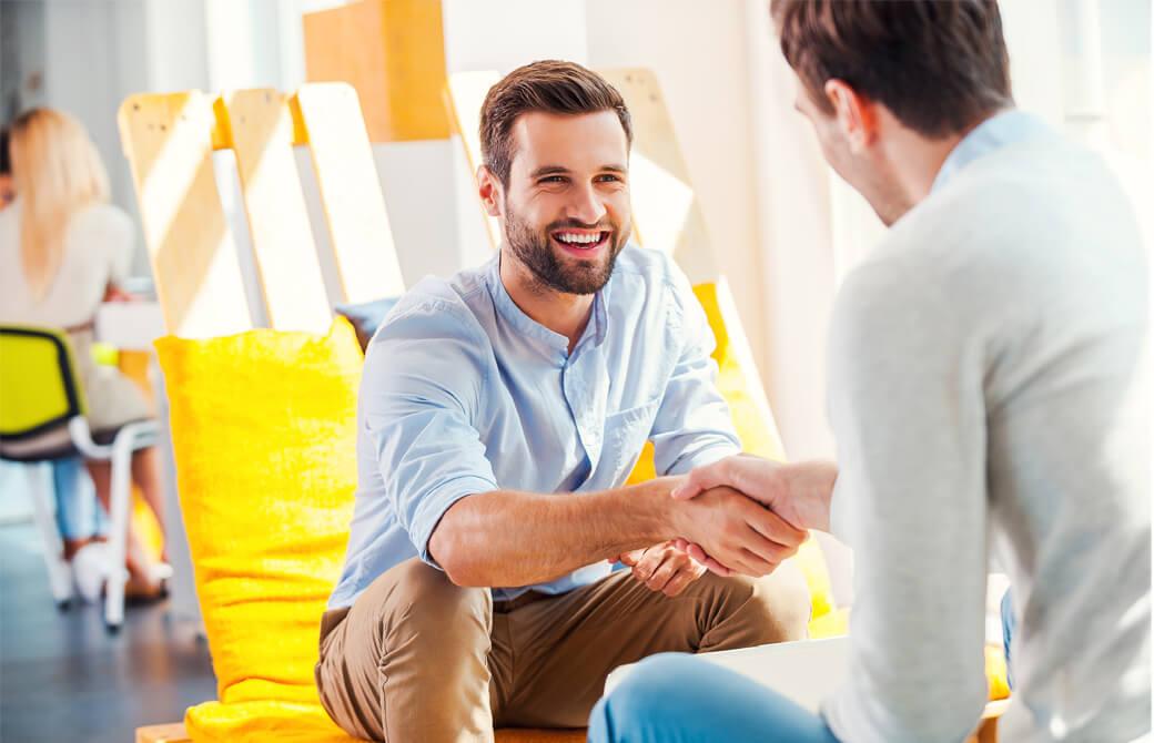 ひげの男性が笑顔で握手をしている
