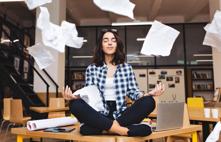 飛び交う書類の間で瞑想をして心を落ち着かせている女性