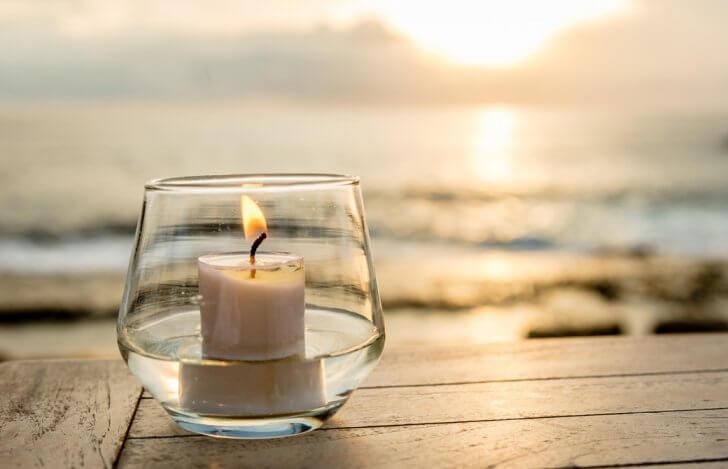 海辺で灯されたグラスの中のキャンドル