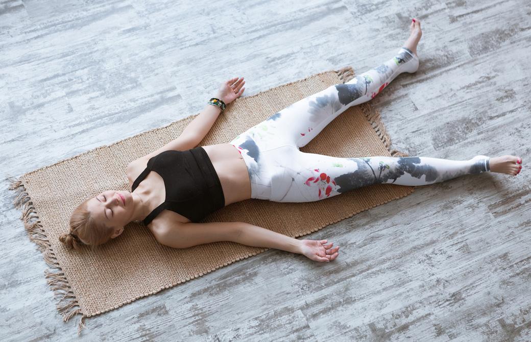 床の上に敷いた布の上でシャヴァーサナをする女性