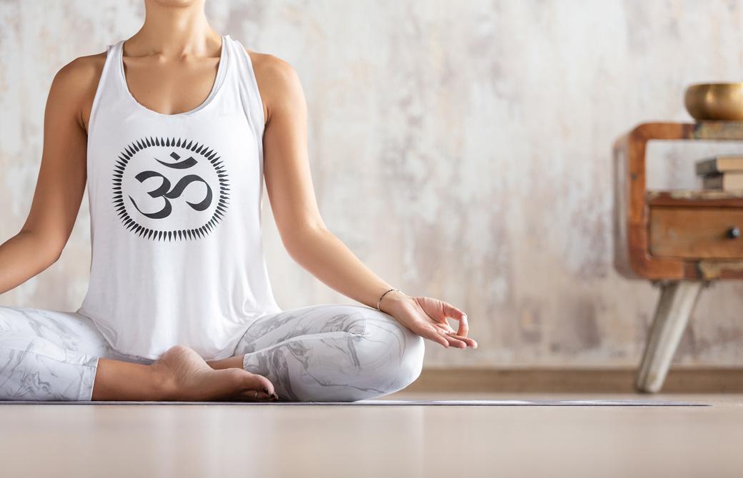 オームのシンボルが描かれたタンクトップを着て瞑想する女性