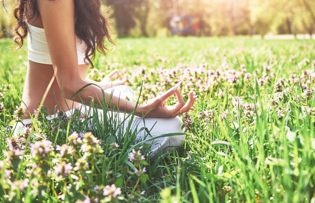 草花の茂る芝生の上であぐらの姿勢で座る女性を横から見たところ