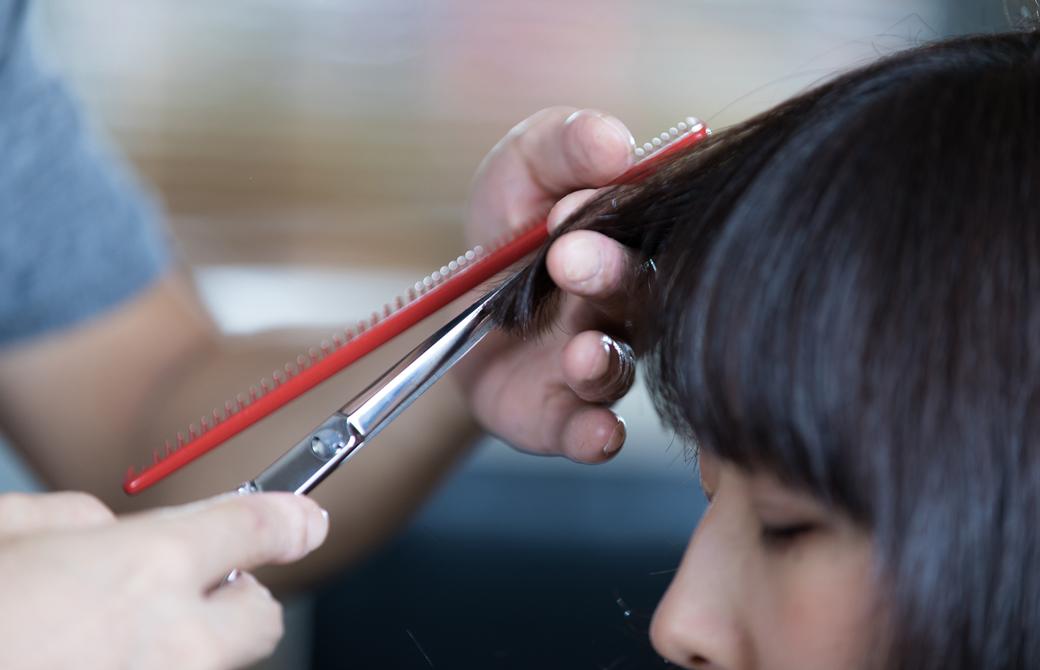 美容師さんに前髪を切ってもらっている女性の横顔