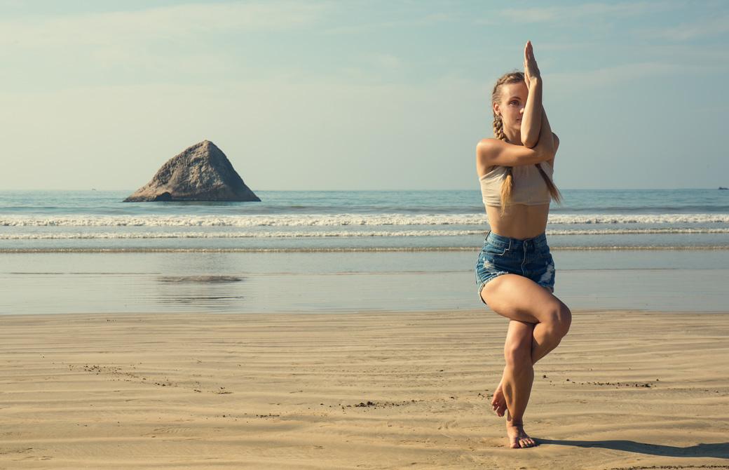 海辺でガルーダアーサナをする女性