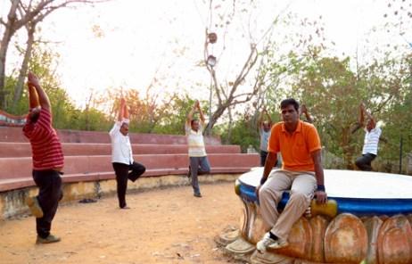 公園でヨガをしている人たちとこちらを見ているインド人男性