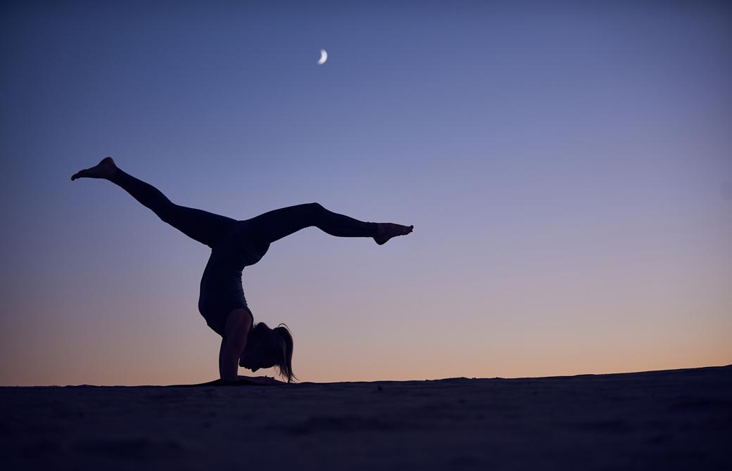 夕暮れ時に月明かりのもと逆転のポーズをとる女性