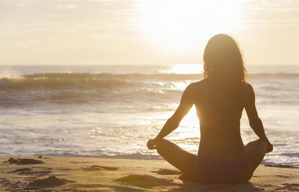 海辺で夕陽をながめて瞑想をする女性