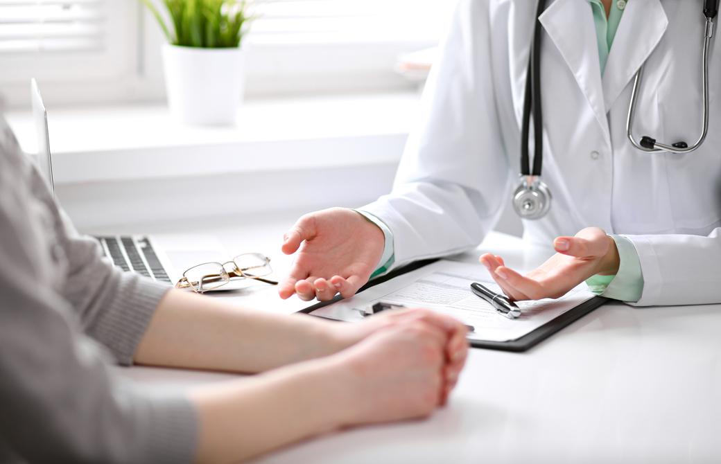 明るい部屋で向き合って座る医師と女性の腕の部分だけ