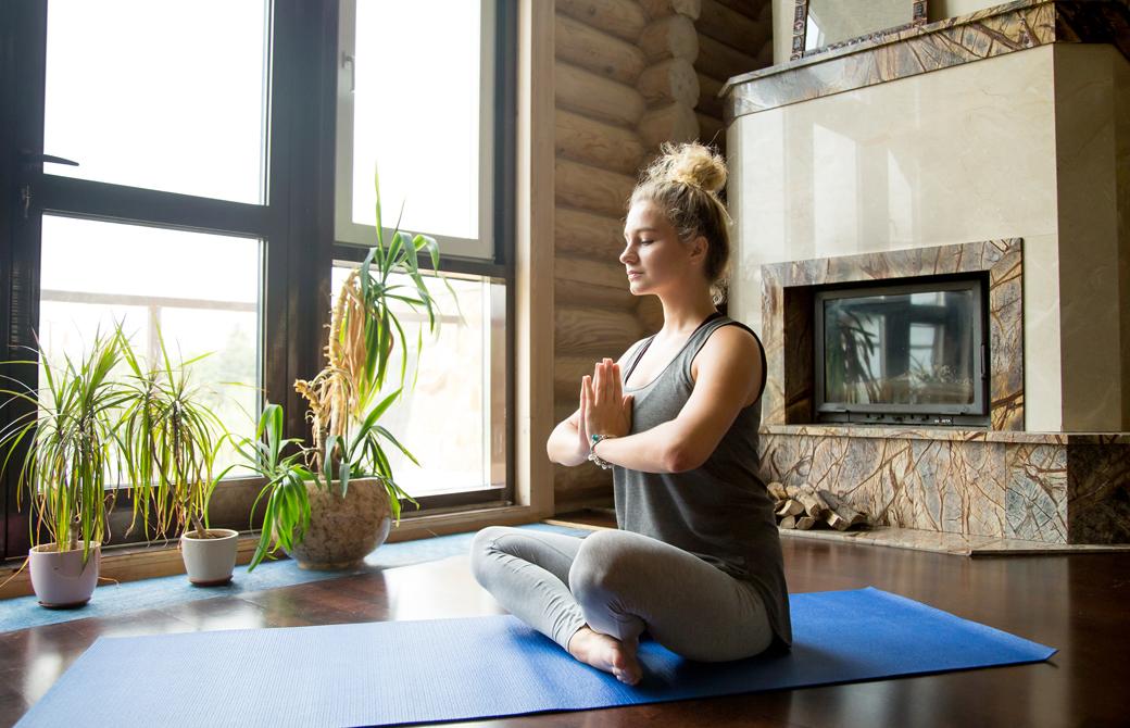 室内のヨガマットの上であぐらの姿勢で手を合わせて瞑想する女性