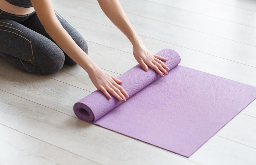 紫色のヨガマットを丸めている女性の手