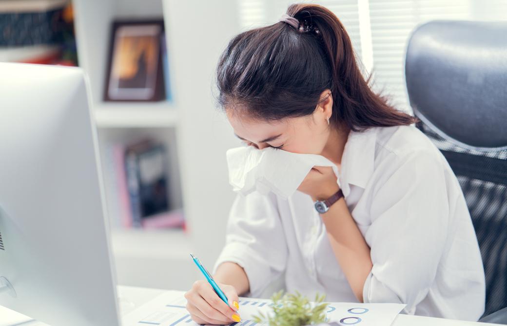 デスクで仕事中の女性がくしゃみを手でおさえている