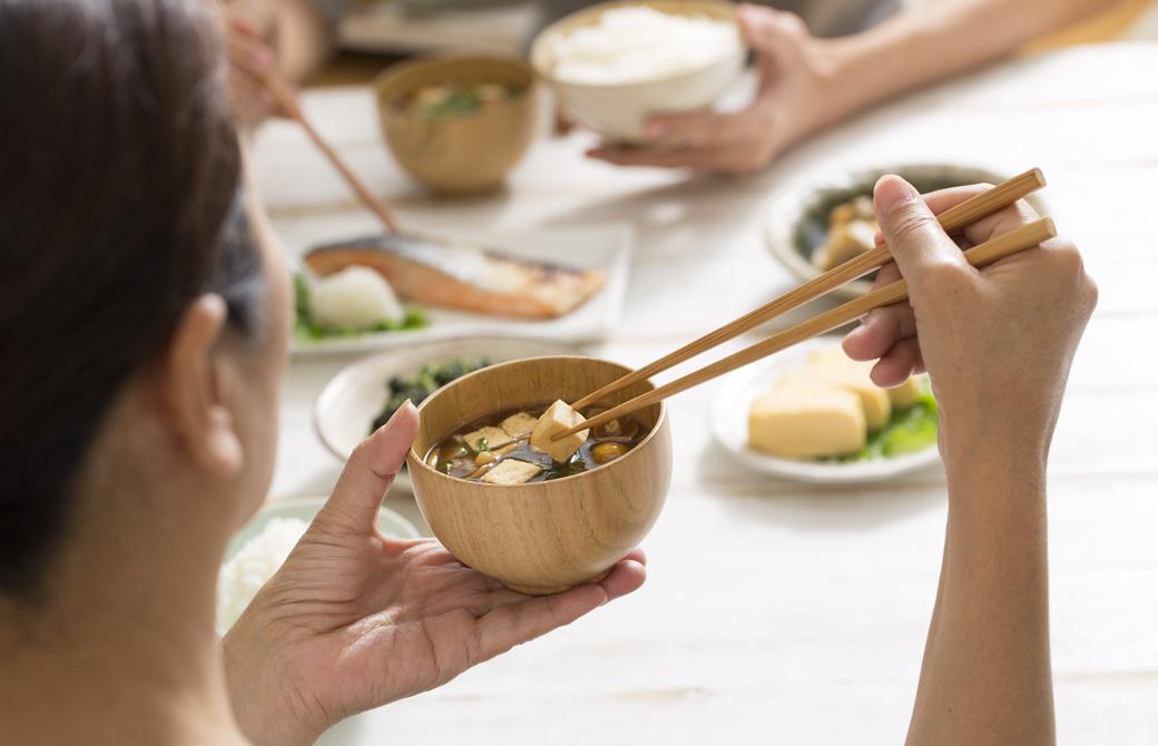 豆腐のみそ汁を飲もうとしている女性と朝食の風景