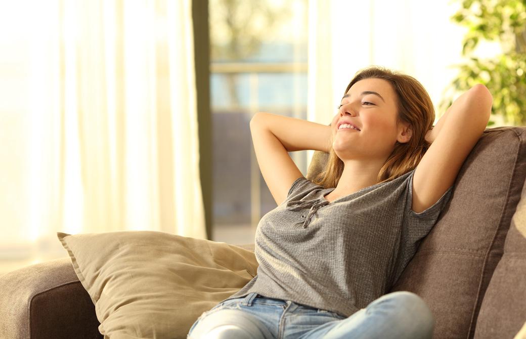 ソファにもたれて微笑みながら伸びをしている女性