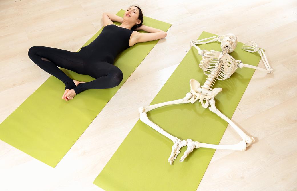 ヨガマットの上でスプタバッタコナーサナをする女性と同じ姿勢の骨模型