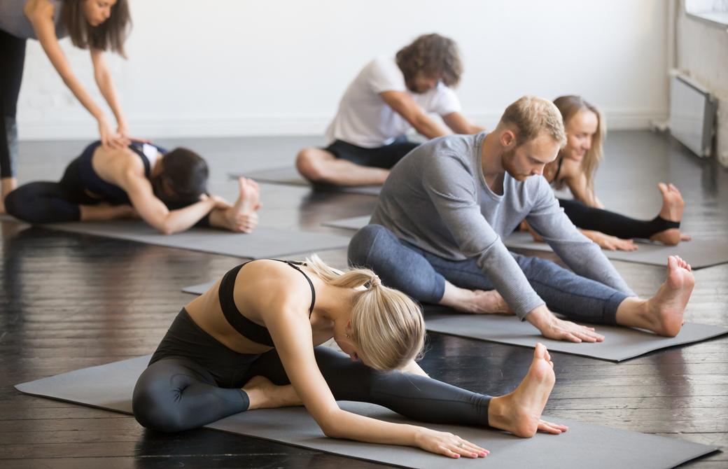 ヨガクラスで膝に頭を付ける前屈ジャーヌシルシャーサナをしている生徒たち