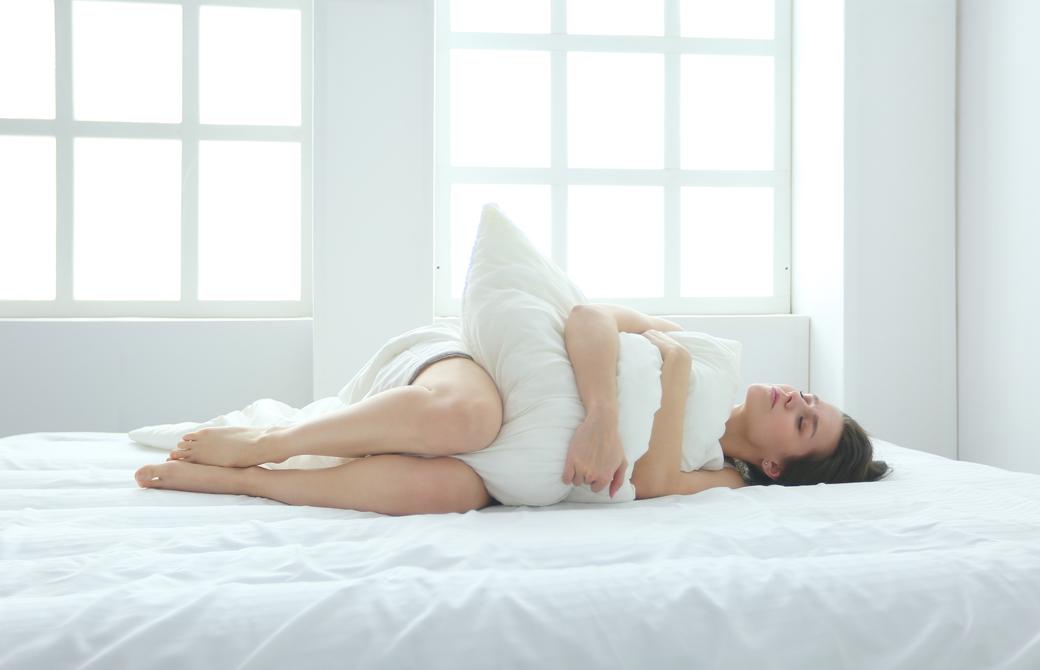 ベッドの上でクッションを抱えて横向きに横になっている女性