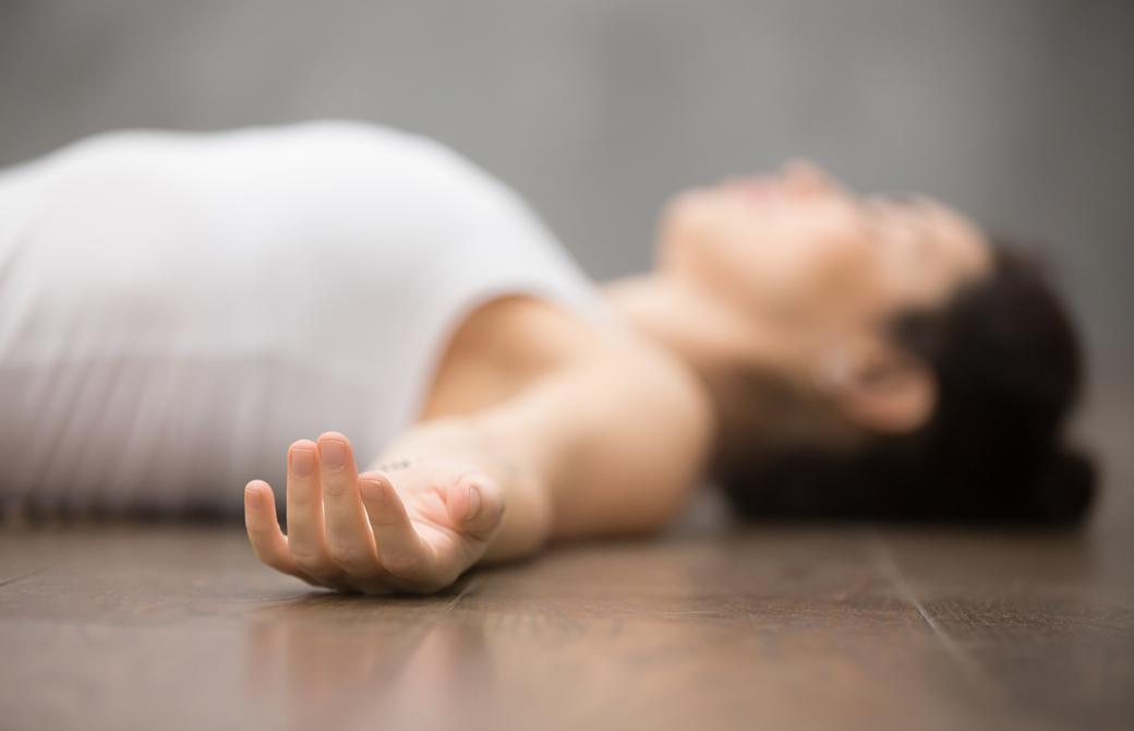 床でシャバアサナをしている女性を横から見たところ