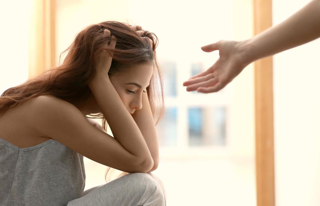 頭を抱えて俯く女性に誰かが手を差し伸べている
