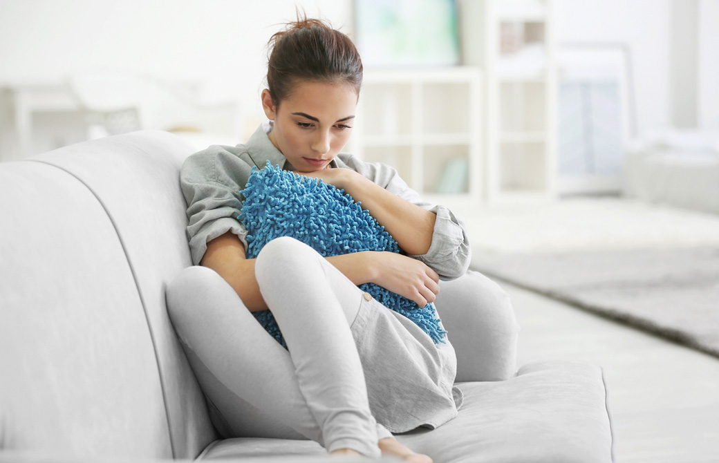 ソファで青いクッションを抱いてうつむいている女性
