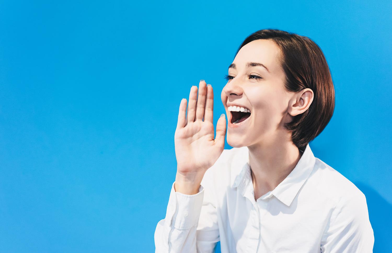 笑顔で口元に手を寄せて大きな声を出しているような女性