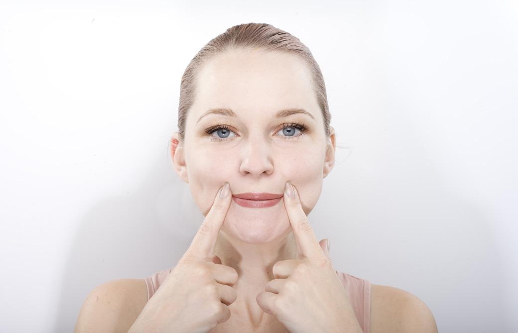 口角を指で引き上げ顔ヨガをしている女性