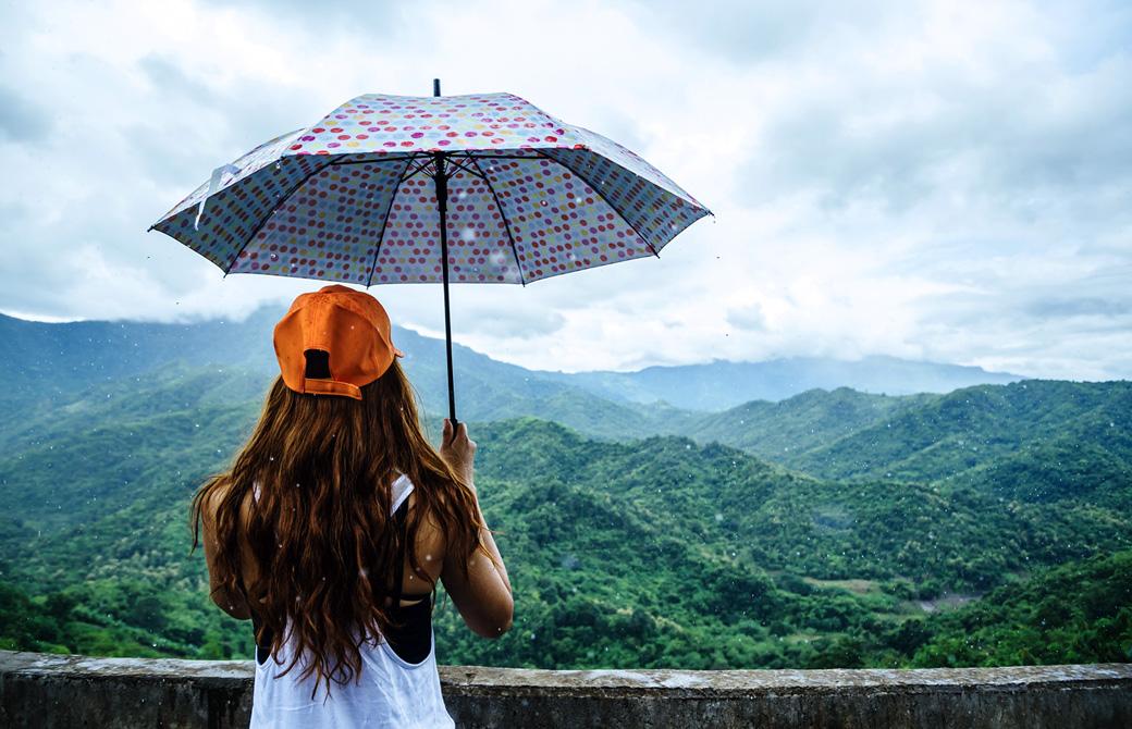 雨の中を美しい山並みに向かって傘をさしている女性の後ろ姿