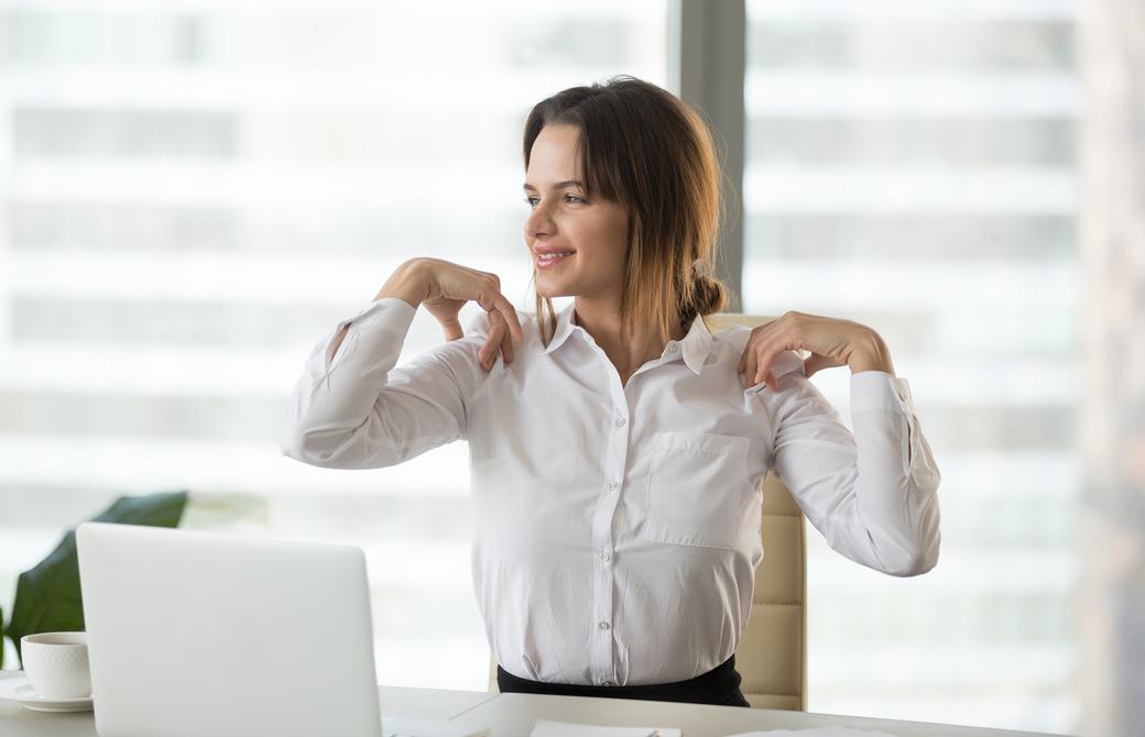 オフィスデスクに座りながら両肩を回して微笑んでいる女性