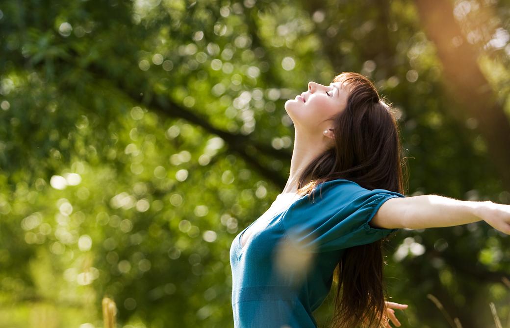 森林の中で女性が空をあおいで気持ち良さそうに両腕を開いている