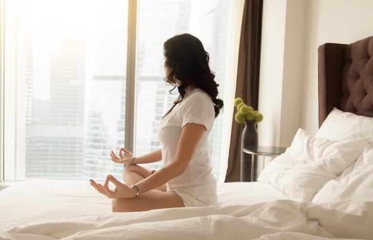 女性が窓際のベッドの上で瞑想のポーズをとっている