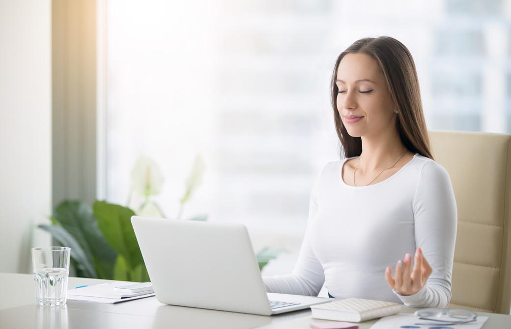 デスクでPCを前に目を閉じ瞑想をしている女性