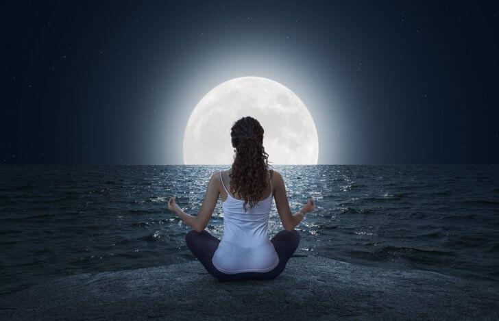 海辺で満月に向かって瞑想をしている女性の後ろ姿
